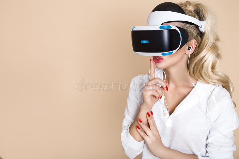 Woman with VR glasses of virtual reality. Young girl in virtual augmented reality helmet. VR headset. stock images