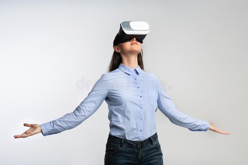 Woman In VR Headset Standing Experiencing Virtual Reality, Gray Background. Woman In VR Headset Experiencing Virtual Reality Standing Over Gray Background royalty free stock photography