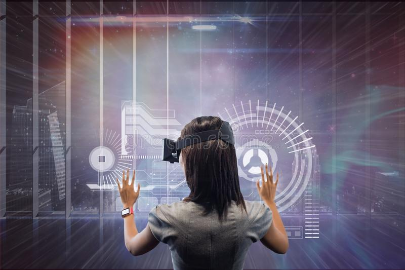 Woman in VR headset touching interface against galaxy and city background. Digital composite of Woman in VR headset touching interface against galaxy and city stock photos