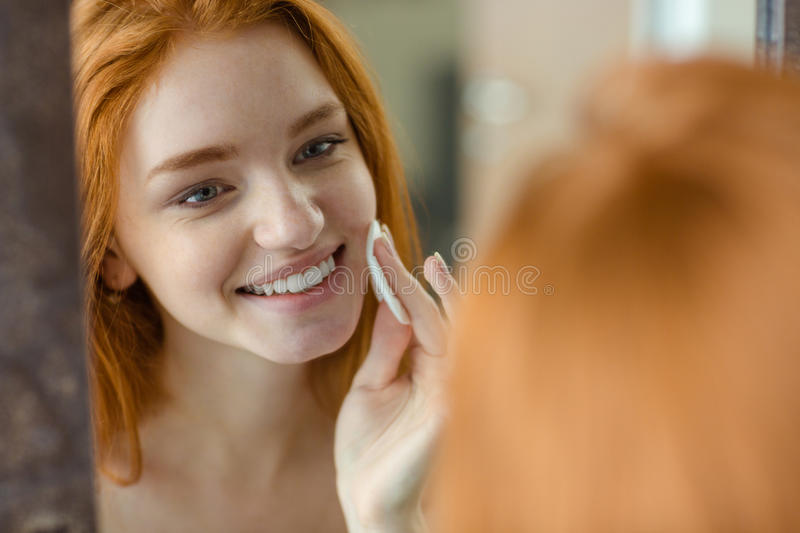 Woman with wadding looking at her reflection in mirror. Portrait of a smiling redhair woman with wadding looking at her reflection in mirror stock images