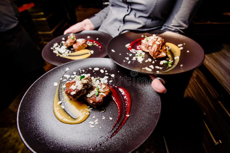 Woman waiter carries three plates of food. Meat steak garnished with two sauces on a dark plate. Close-up. Wide angle photography royalty free stock photography