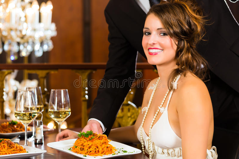 Woman and waiter in fine dining restaurant. Pretty women sitting at a table in a fine dining restaurant, waiter served the dinner - a large chandelier is in stock images