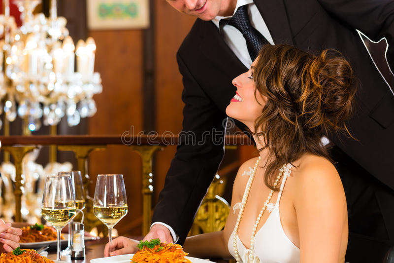 Woman and waiter in fine dining restaurant. Pretty women sitting at a table in a fine dining restaurant, waiter served the dinner - a large chandelier is in royalty free stock photos