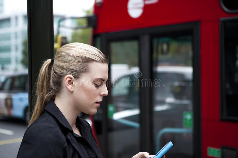 Woman waiting at bus stop with mobile phone in London royalty free stock images