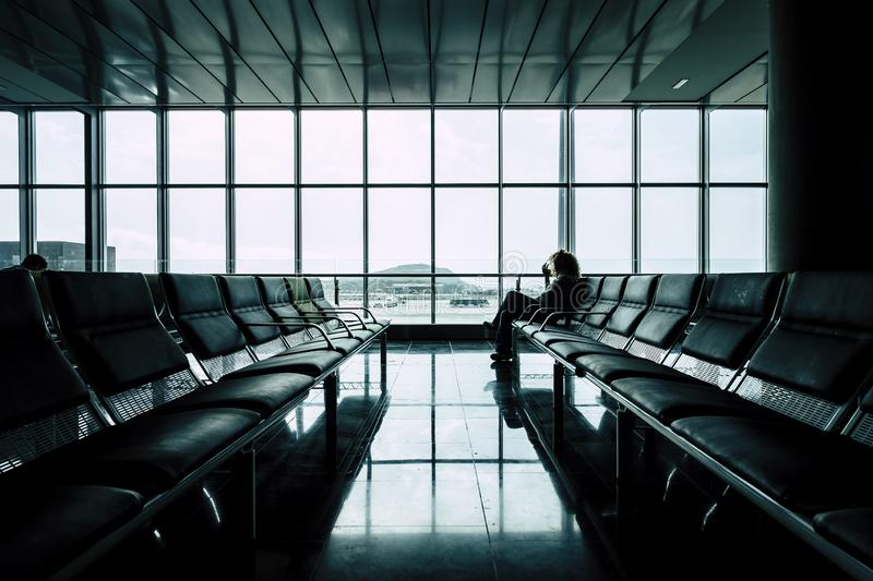 Woman waiting for her flight at the airoport in  the gates area - delay airplane on arrival or departures concept - people on. Travel sit down on the seats royalty free stock photo
