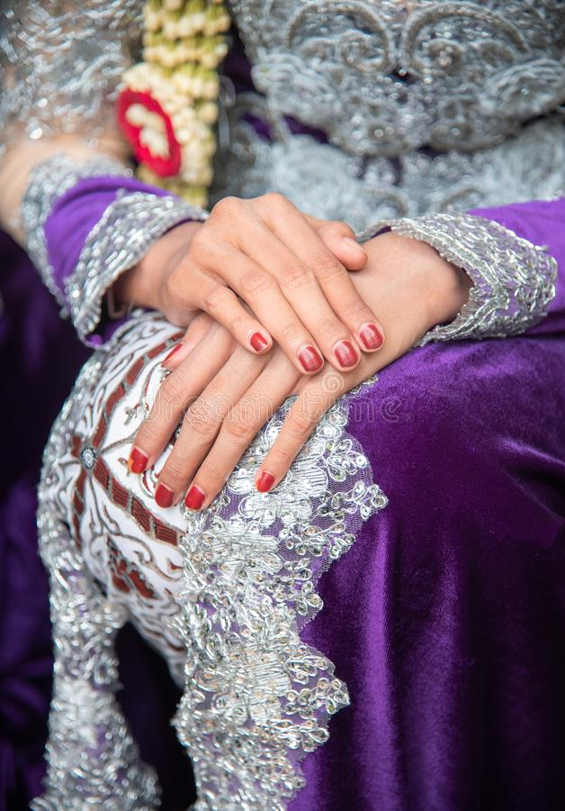 Woman waiting with her hand on knee. She is wearing traditional Javanese wedding dress stock photo