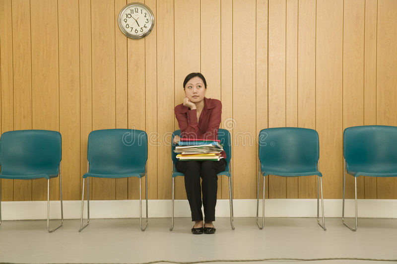 Woman in Waiting Room. Young Asian woman looking bored in a waitng room royalty free stock photo