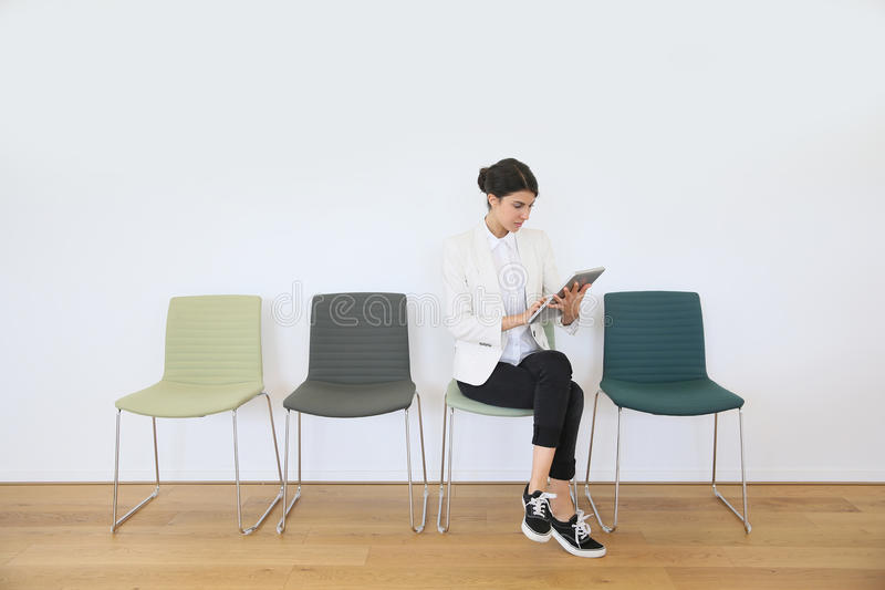 Woman in waiting room on tablet stock images