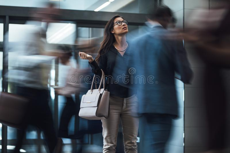 Woman waiting during rush hour in lobby stock images