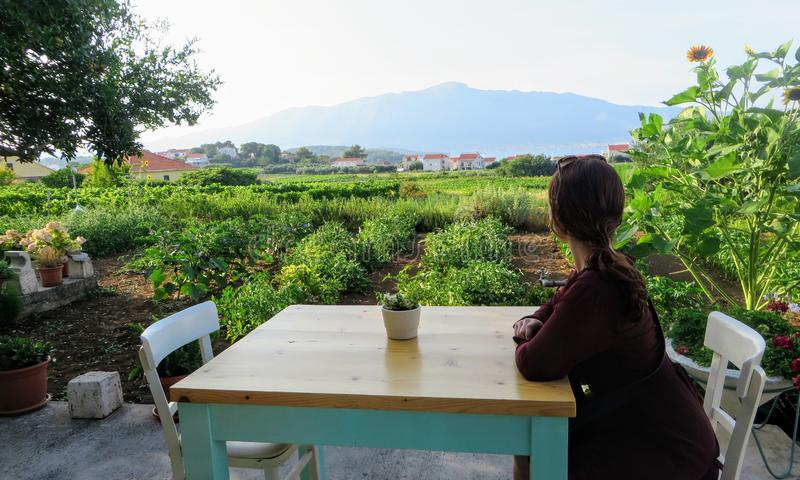 A woman waiting at a table ready to enjoy a meal with a view of a sprawling wine vineyard growing the local grk grapes royalty free stock images