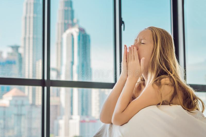 Woman wakes up in the morning in an apartment in the downtown area with a view of the skyscrapers. Life in the noise of the big ci. Ty concept. Not enough sleep royalty free stock photography