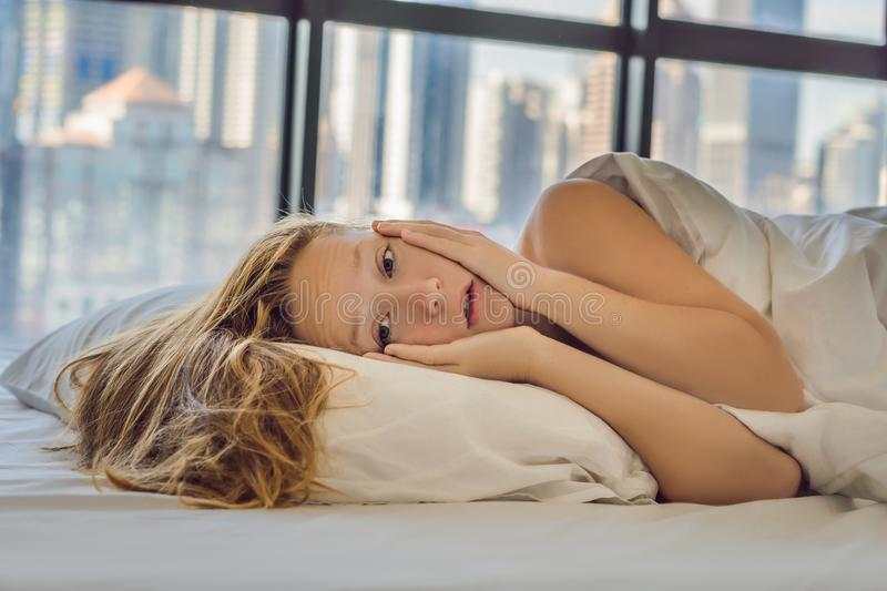Woman wakes up in the morning in an apartment in the downtown area with a view of the skyscrapers. Life in the noise of the big ci. Ty concept. Not enough sleep royalty free stock images