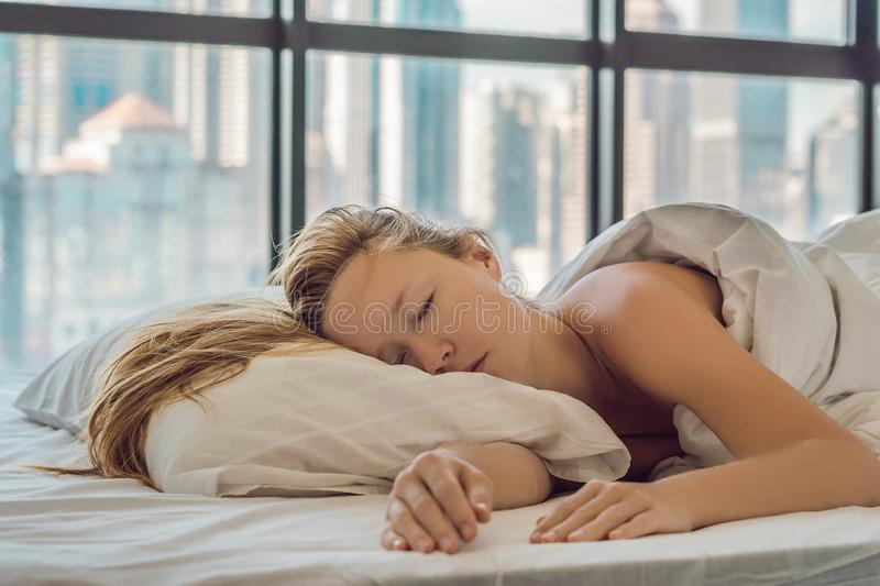 Woman wakes up in the morning in an apartment in the downtown area with a view of the skyscrapers. Life in the noise of the big ci. Ty concept. Not enough sleep royalty free stock image