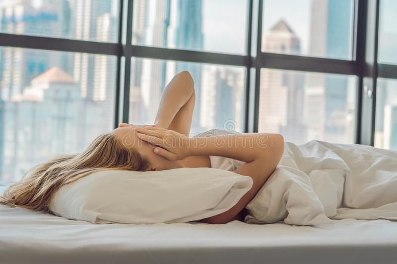 Woman wakes up in the morning in an apartment in the downtown area with a view of the skyscrapers. Life in the noise of the big ci. Ty concept. Not enough sleep stock image