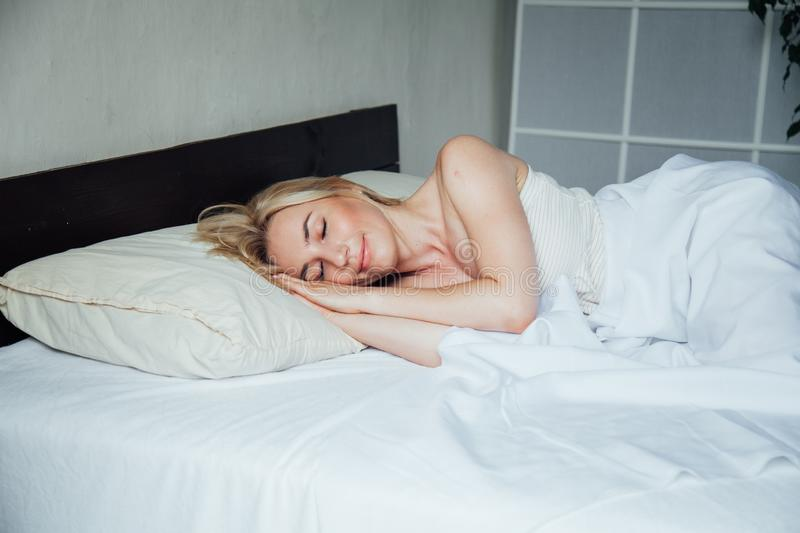 Woman blonde wakes up after sleep in bedroom on bed stock photos