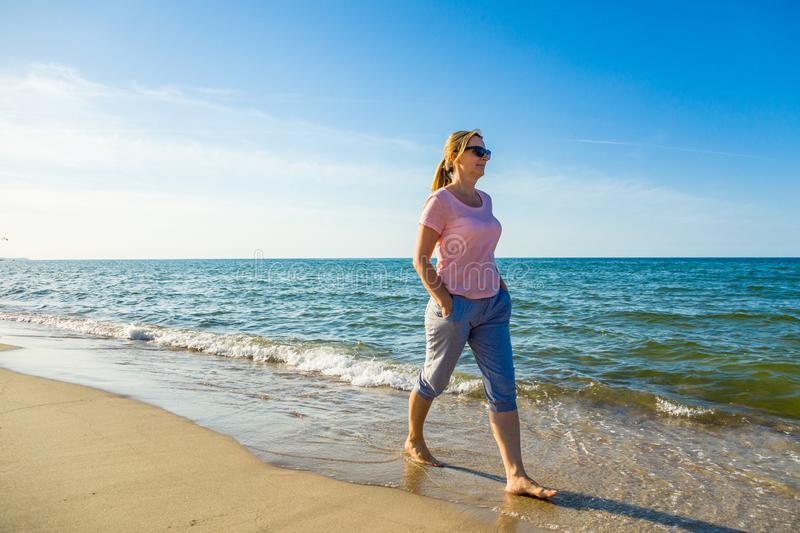 Woman waking on beach. Middle-age woman waking on beach royalty free stock images