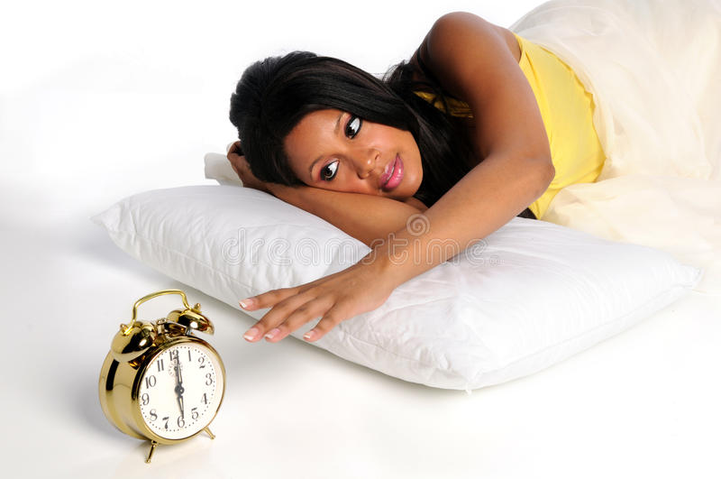 Woman Waking Up. African American woman waking up extending hand to retro alarm clock stock image