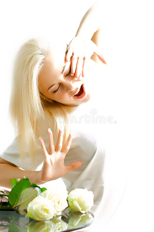 Woman waking up. A blond woman waking up in the morning, white flowers by her bed stock photography