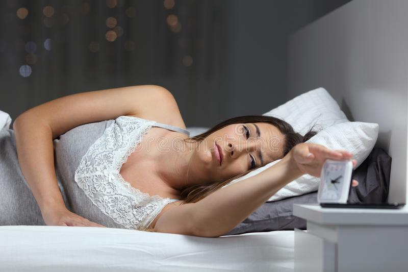 Woman waking up in the night turning off alarm clock. Tired woman on a bed waking up in the night turning off alarm clock stock photography