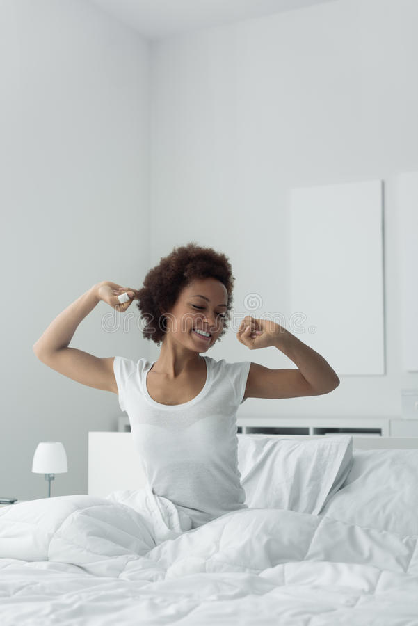 Woman waking up and stretching. Young african woman waking up early in the morning, she is sitting in her bed and stretching stock photos