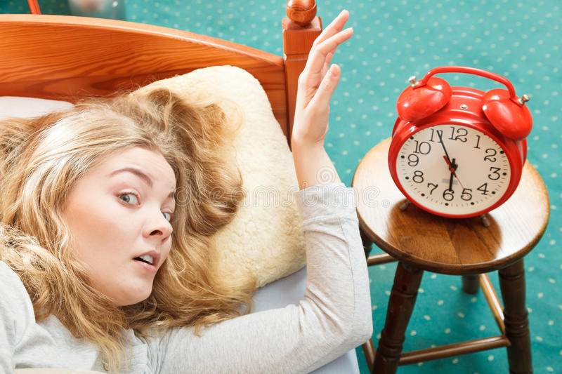 Woman waking up turning off alarm clock in morning. Woman waking up in bed turning off alarm clock. Young girl in the morning royalty free stock photos