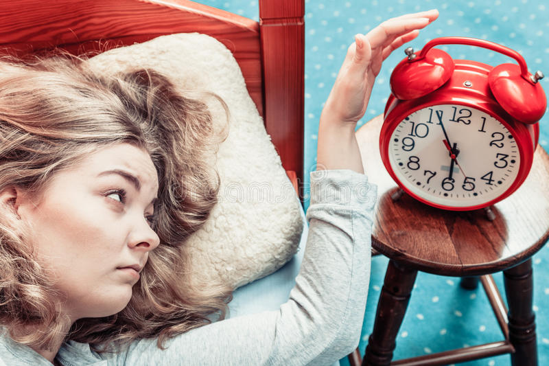 Woman waking up turning off alarm clock in morning. Woman waking up in bed turning off alarm clock. Young girl in the morning stock photo