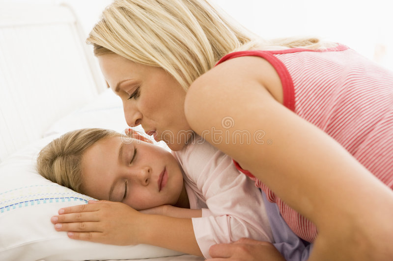 Woman waking young girl in bed with a kiss stock image