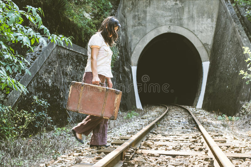 Woman walk on railroad with a suitcase in hands stock photos