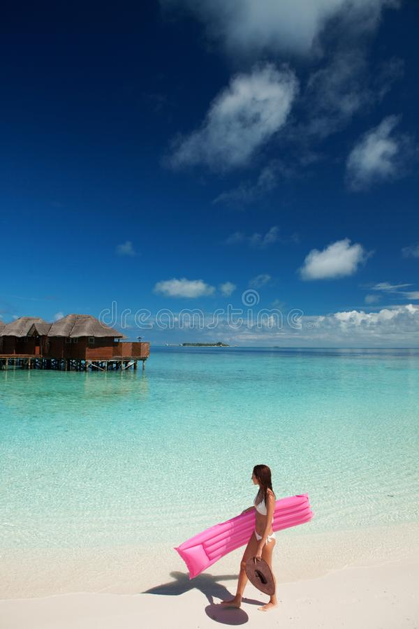Woman walk and relax with inflatable mattress in the sea. Happy island lifestyle. White sand, crystal-blue sea of tropical beach. royalty free stock photo