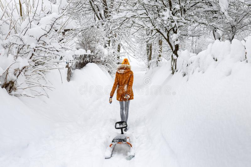 Woman walk sled alone snowfall, winter snow cold weather outdoor sledge countryside blizzard royalty free stock photos