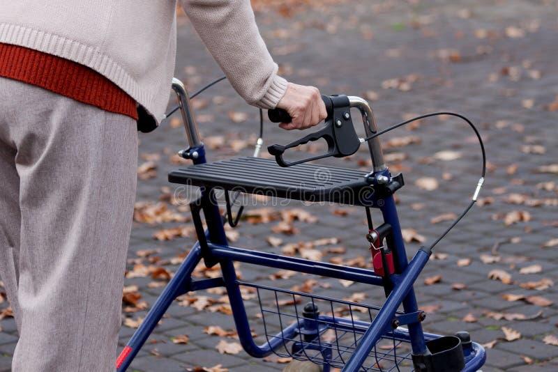 Woman with walker. Elderly woman using a walker on a street stock images