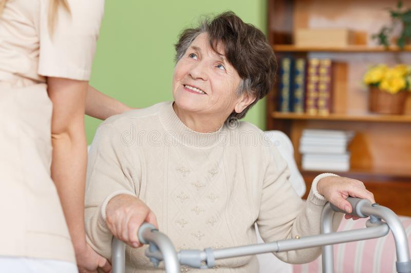 Woman with a walker. Senior women using a walker and caregiver helping her stock images