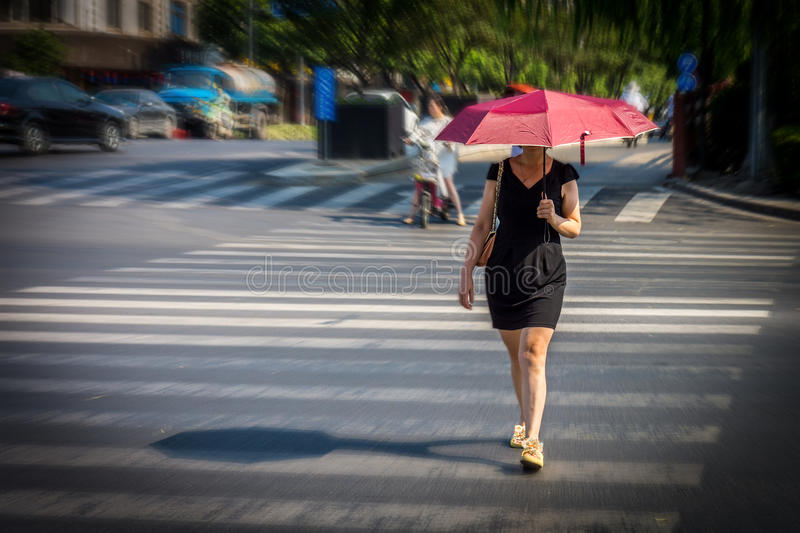 Woman is walking across the street at crosswalk stock photos
