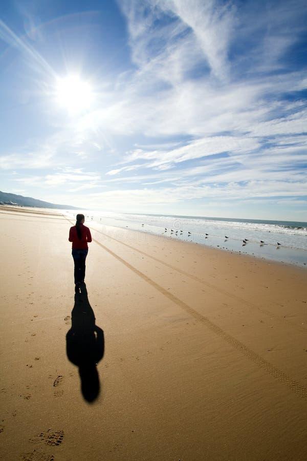 Woman walking alone. Woman silhouette walking alone at the beach stock image