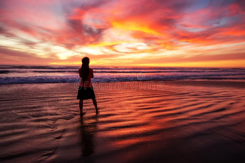 Woman walking alone on the beach in the sunset stock image
