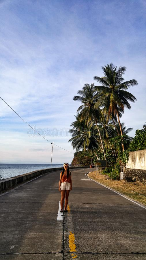Woman alone at the road with palm trees in Cebu Island. Woman walking alone at the empty road with lots of palm trees in Cebu Island in Philippines royalty free stock photos