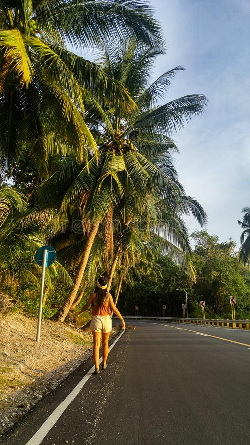 Woman alone at the road with palm trees in Cebu Island. Woman walking alone at the empty road with lots of palm trees in Cebu Island in Philippines royalty free stock photography