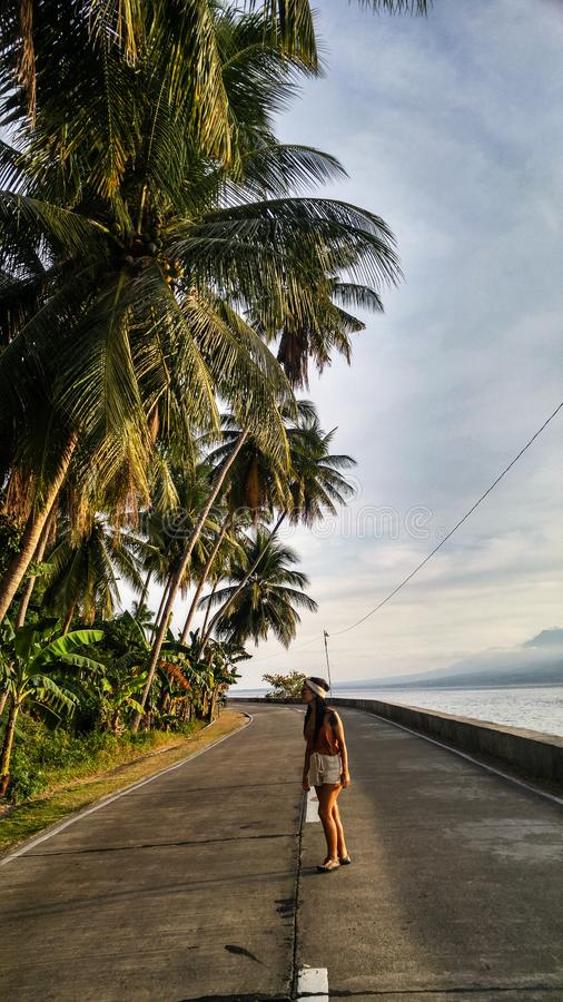 Woman alone at the road with palm trees in Cebu Island. Woman walking alone at the empty road with lots of palm trees in Cebu Island in Philippines royalty free stock image