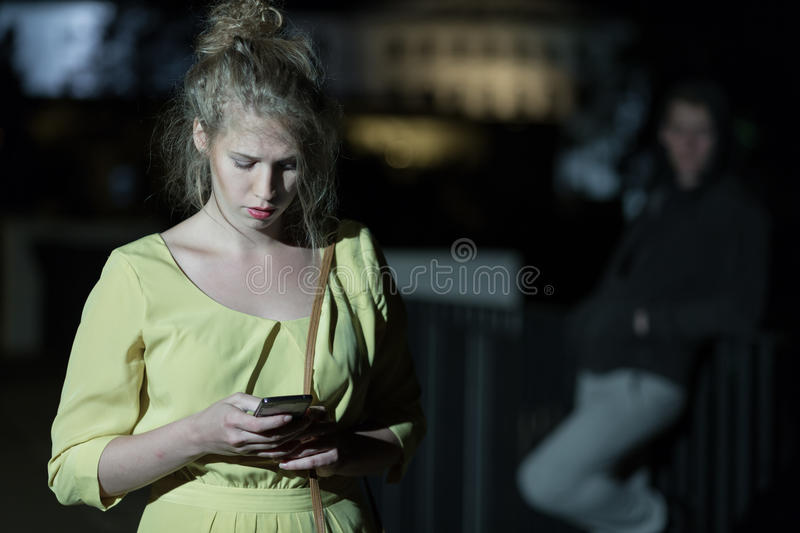 Woman walking alone at night. Woman with mobile phone walking alone at night royalty free stock photography