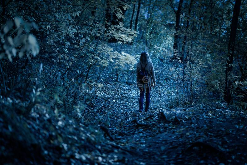 Woman walking alone on path in mystic dark forest. Lonely adult girl in strange creepy park at night in autumn royalty free stock photography