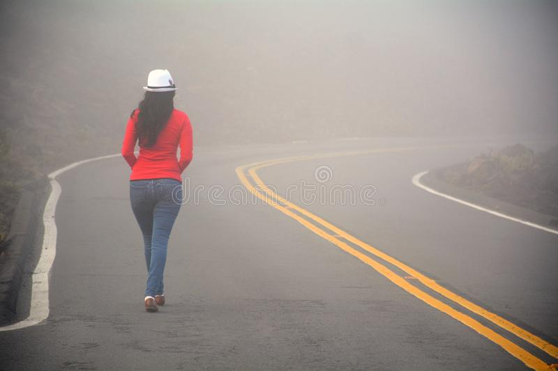 Woman walking alone on the road in the fog stock photo