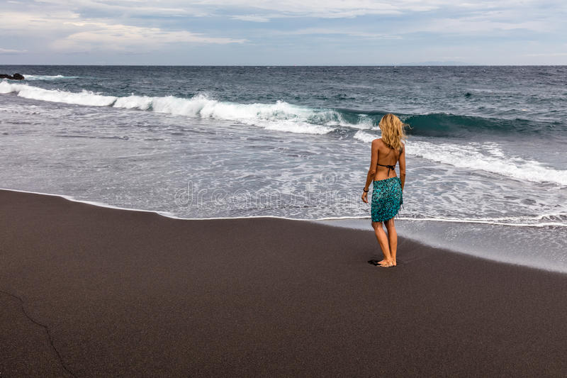Woman walking along black sand beach in Padangbai, Bali Island, Indonesia. Woman walking along black sand beach, Padangbai, Bali Island, Indonesia royalty free stock images