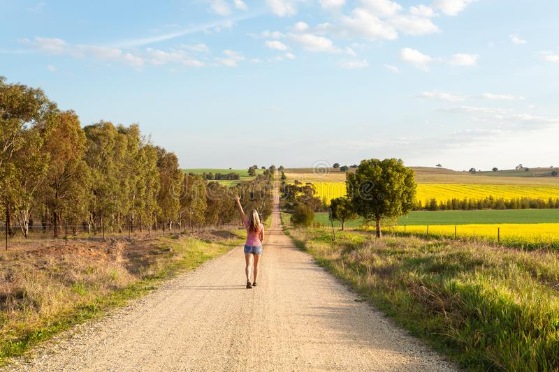Woman walking along a dusty road among the rural fields stock photos