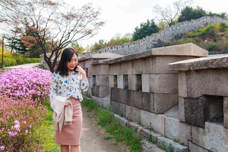 Woman walking along the Seoul City Wall. Asian young woman walking along the Seoul City Wall stock photo