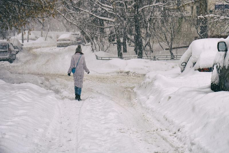 Woman walking along a snowbound Moscow street in February. Young woman walking along a snowbound Moscow street in February royalty free stock images