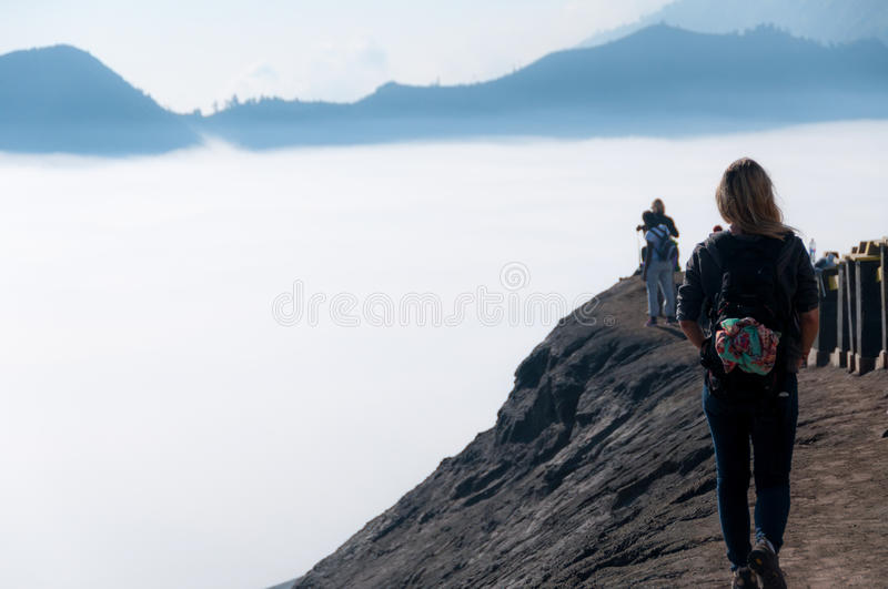 Woman walking along top of volcano next to fog and. Mist of the sulphur volcano Bromo stock photos