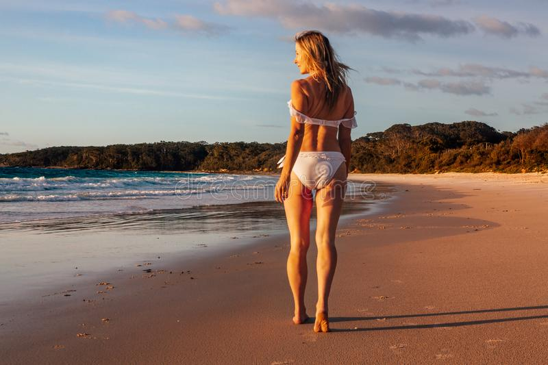 Woman walking along the wet sand of the beach early morning royalty free stock image