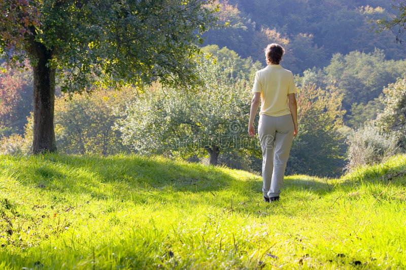 Woman walking in a autumn landscape royalty free stock photography