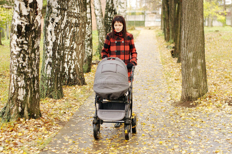 Woman walking in autumn park with baby buggy stock photography