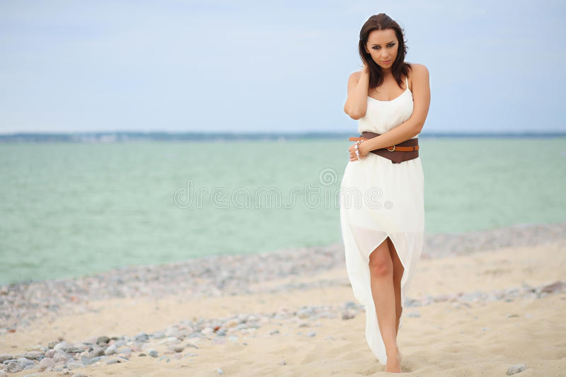 Woman walking on the beach stock images
